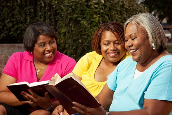 Small group of women talking and reading the Bible.